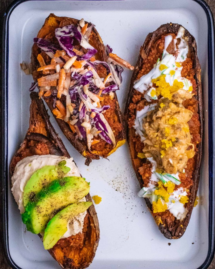 sweet potato toasts laying in white metal tray, topped with avocado and hummus, 1 with purple cabbage slaw and 1 sour cream and aubergine