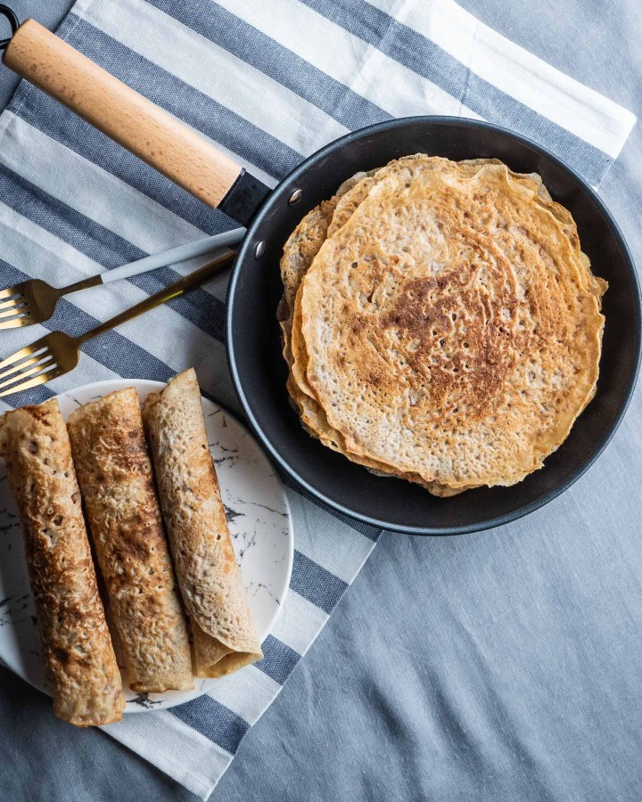 flatlay of vegan protein pancakes crepes in place pan with wooden handle next to plate with rolled up crepes lying on top on blue and white pinstripe cloth