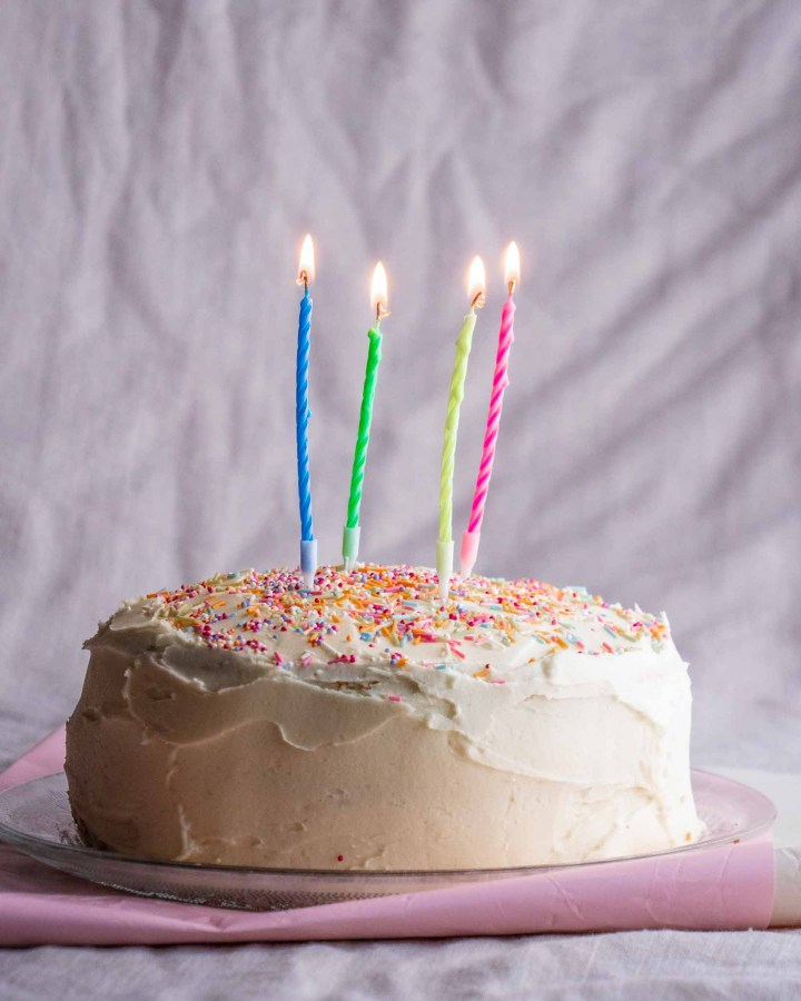 birthday cake covered in white cream cheese frosting, colourful hundreds and thousands sprinkles and lit candles