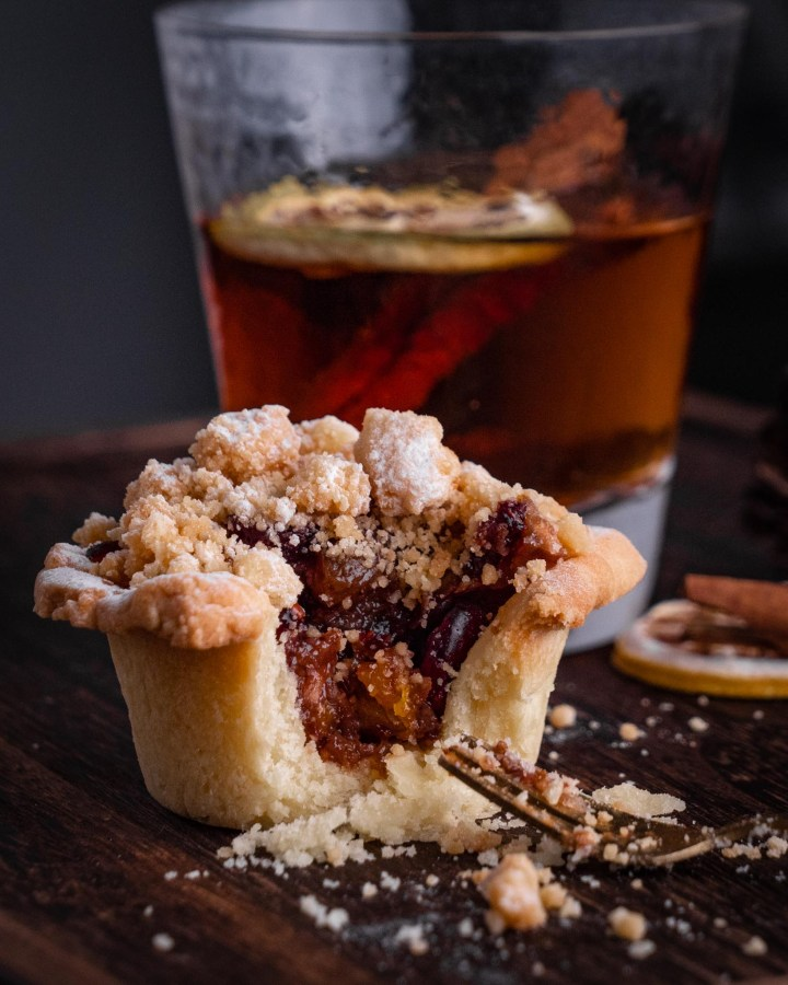 homemade christmas vegan mince pie filled with juicy raisins with forkful taken out and surrounded in pastry crumbs on wood table