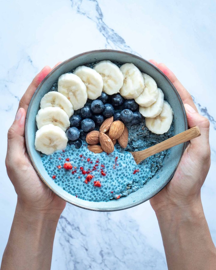 hand holding large bowl filled with blue overnight oats topped with blue chia pudding, banana slices, blueberries, almonds and strawberry bits
