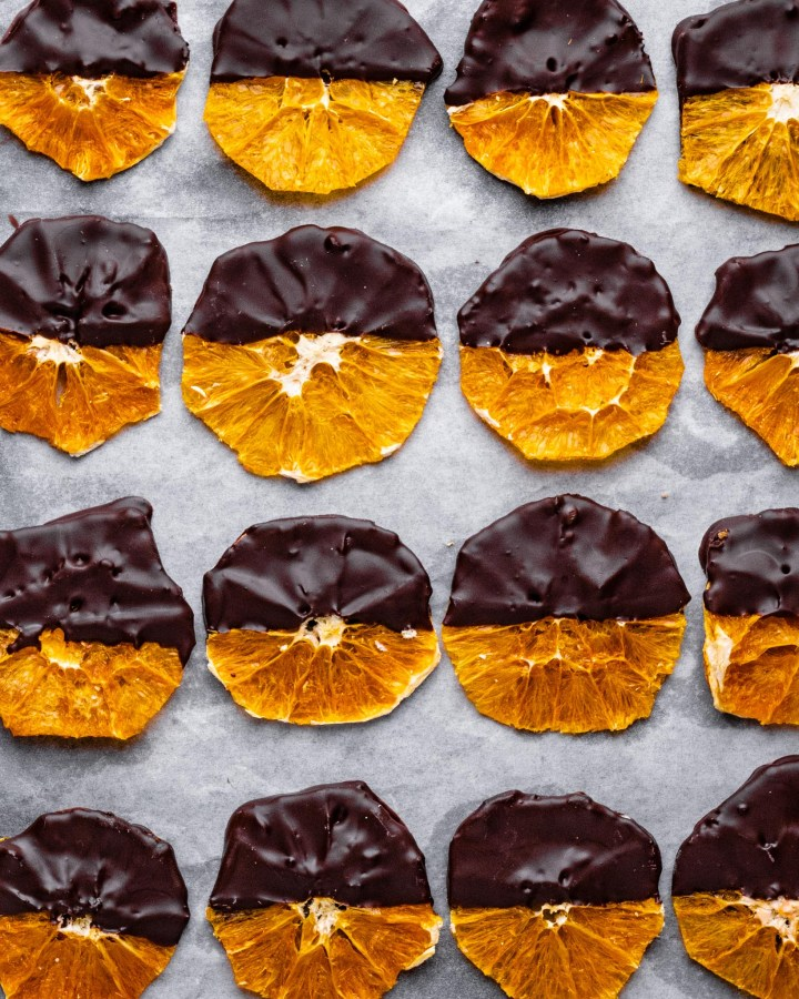 several dehydrated orange slices half-covered in dark chocolate lined in neat rows on white parchment paper