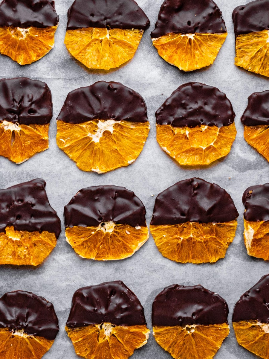 dehydrated orange slices half covered in dark chocolate laid out in neat rows on white parchment paper