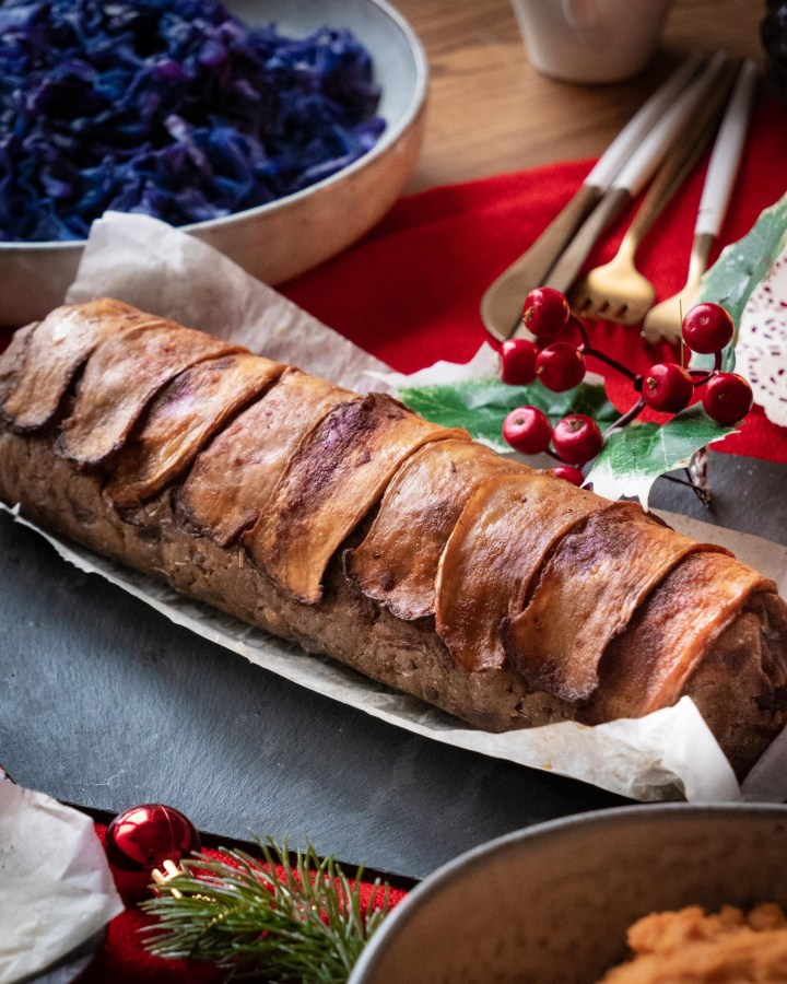 entire vegan stuffing in long log shape topped with mushroom bacon slices on table decorated with festive plants and christmas food