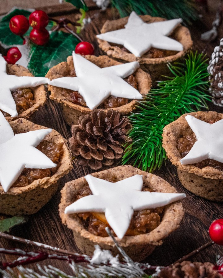 individual mini mince pies topped with white fondant stars on wooden table scattered with rustic christmas decorations