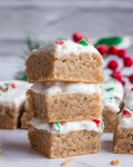 peppermint blondie chunks stacked on top of one another topped in frosting and crushed red and green candy canes on white marble table