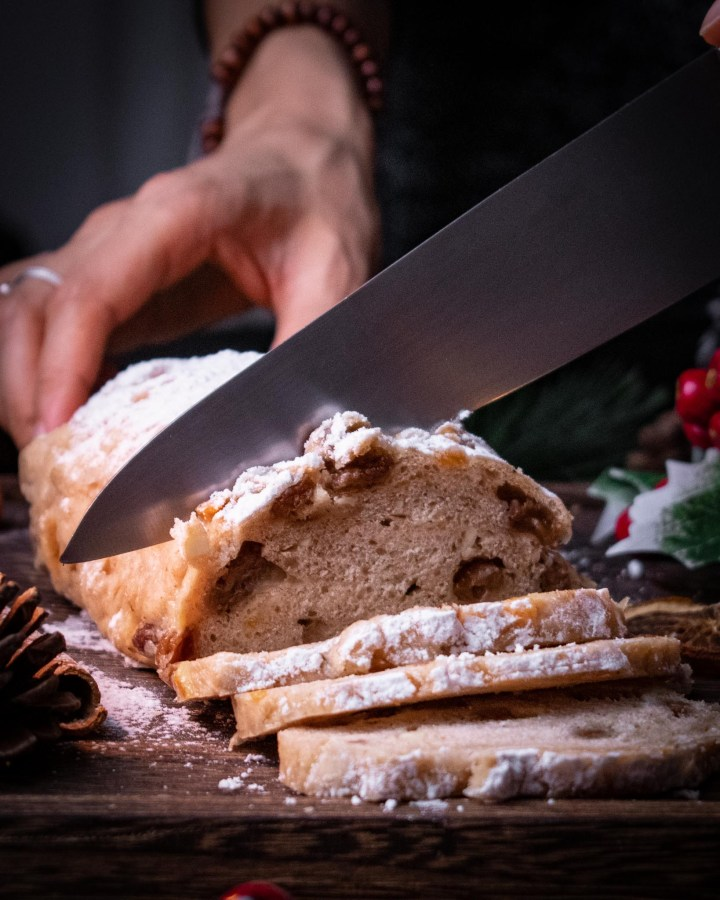 christmas vegan stollen being sliced to reveal inside of loaf studded with raisins