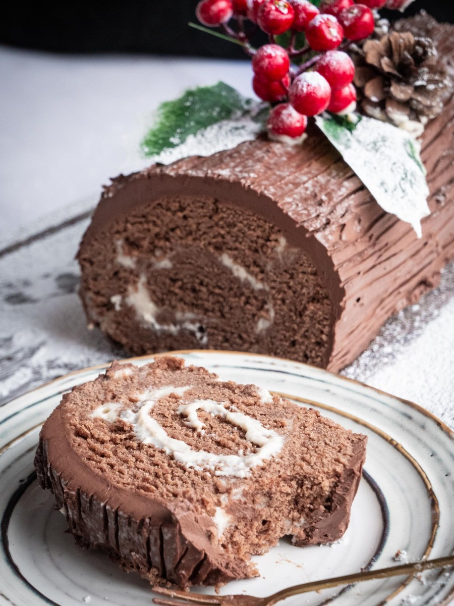 vegan chocolate yule log sliced to reveal centre with swirls of white cashew cream and topped with holly sprigs and berries next to slice