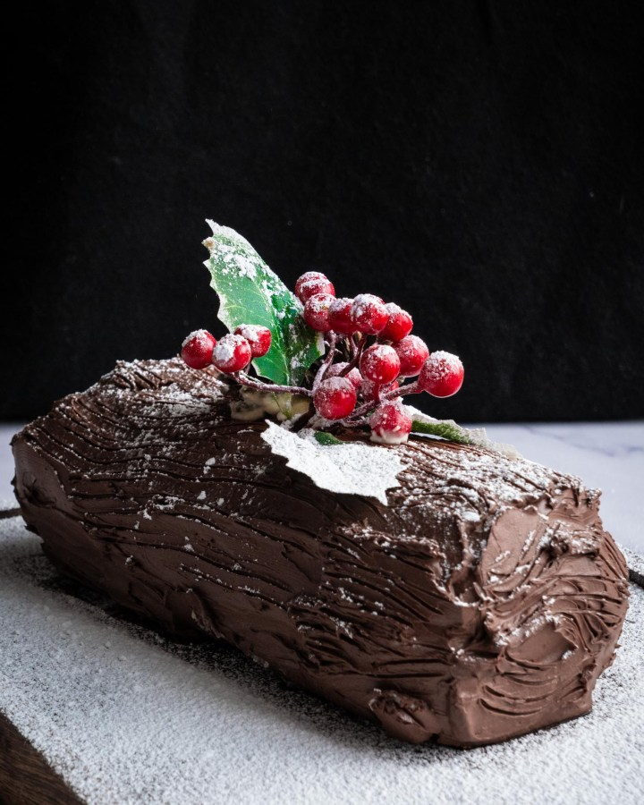 full chocolate swiss roll topped with holly and pinecones and laying on surface dusted entirely with powdered sugar