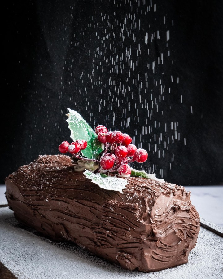 whole chocolate yule log with powdered sugar being sprinkled on top like snow with black background and white surface on base