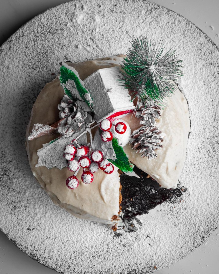 flatlay christmas cake on wooden board scattered with powdered sugar like snow topped with red wooden house, holly and pinecones