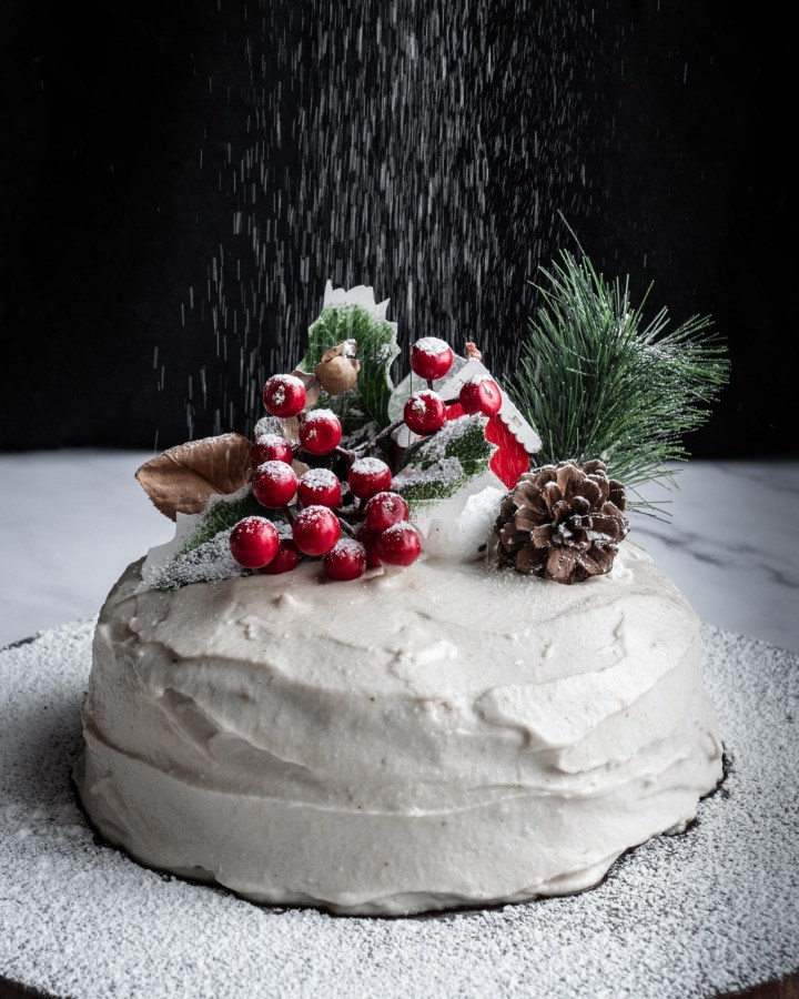 magical chrstmas cake being sprinkled with powdered sugar against black background like snow