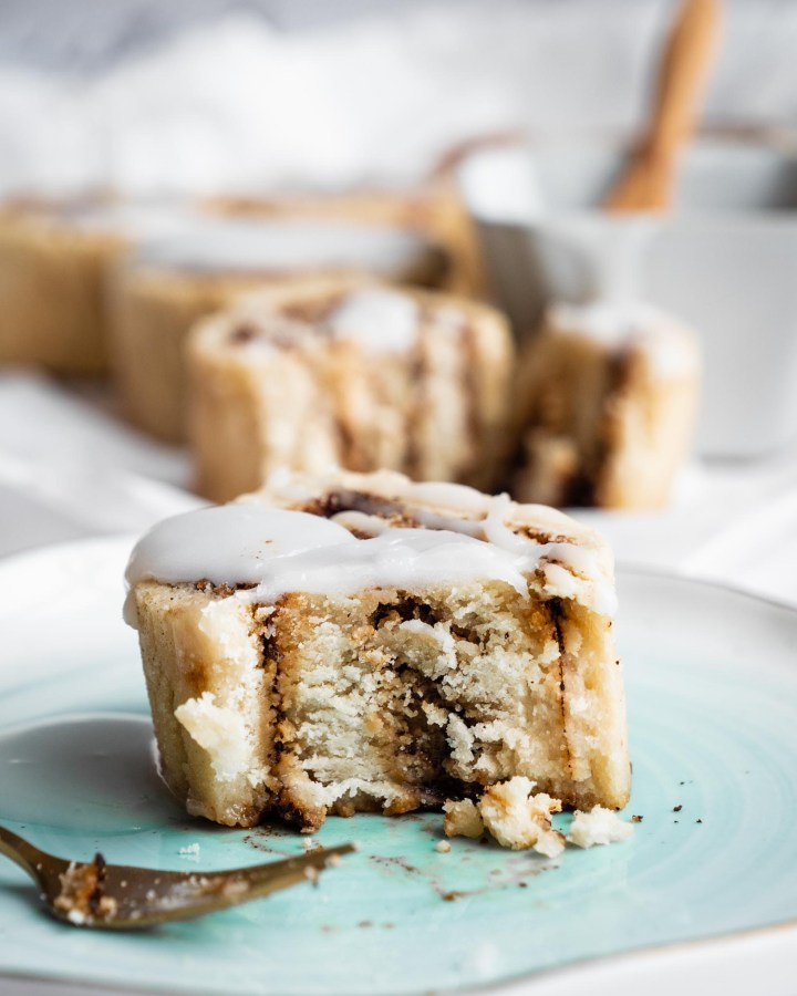 cinnamon bun on plate cut in middle with swirls of cinnamon inside an almond flour bread and drizzled with white frosting