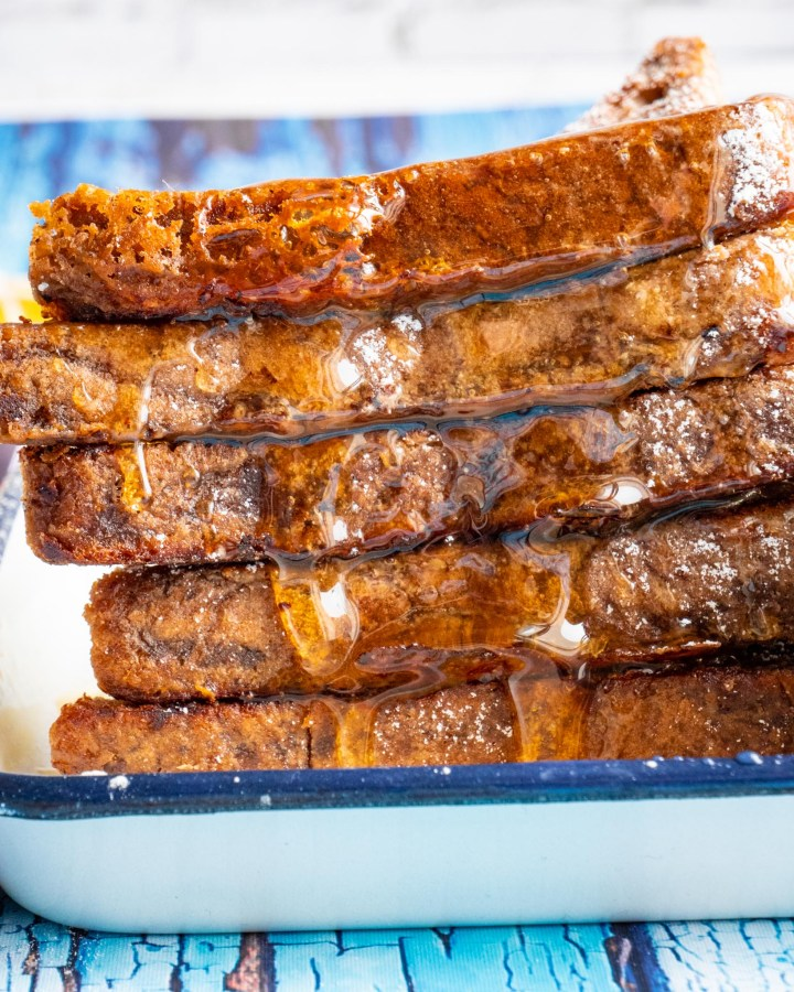 slices of french toast in large stack lined up neatly dripping with maple syrup