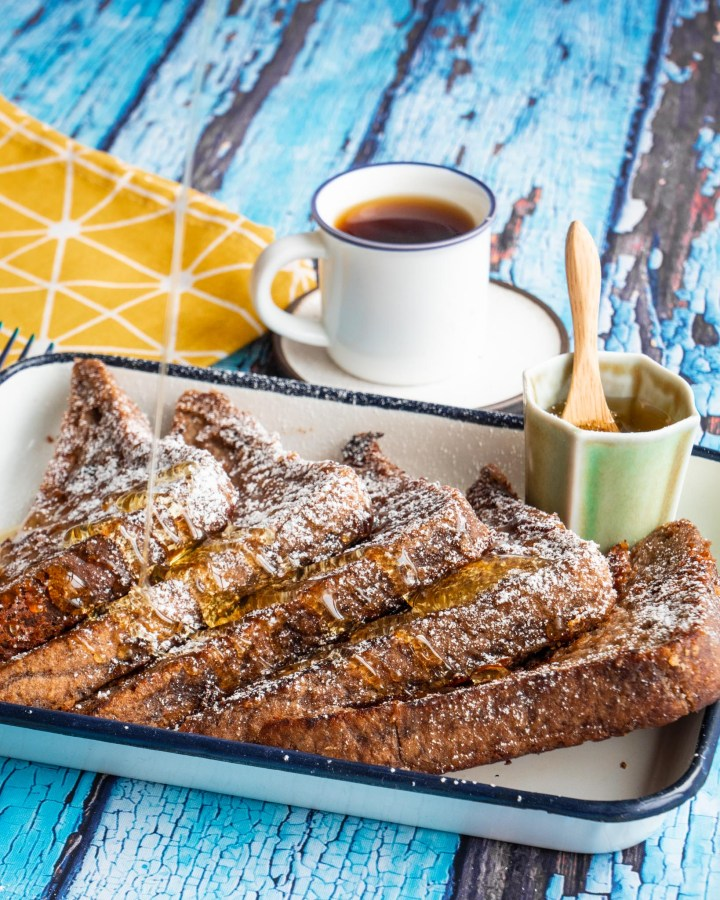 6 slices of crisp golden brown french toast triangles in white enamel tray on blue rustic wooden table next to pot of syrup and espresso cup