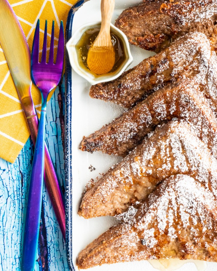 french toast slices dusted with icing sugar on white tray laid on top of rustic vibrant blue wooden table next to metallic purple pink cutlery
