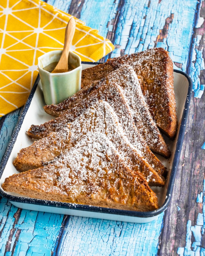 golden brown toast slices dusted with icing sugar on white vintage tray on blue wooden table