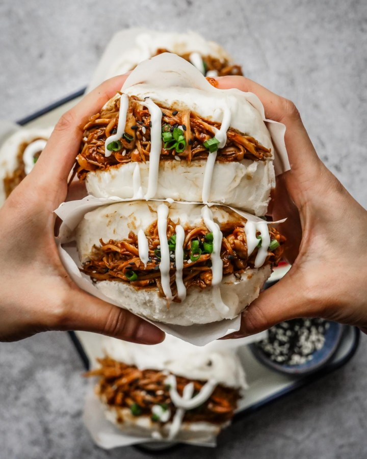 hands holding large chinese style bao buns stuffed generously with sticky vegan pulled pork and dripping with mayonnaise