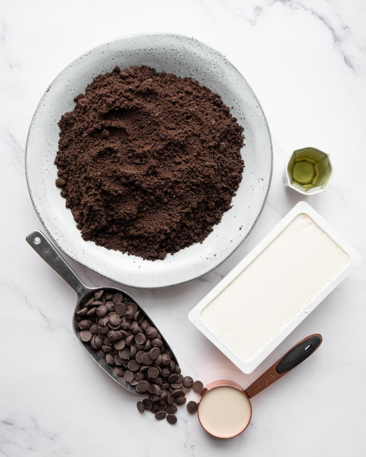 ingredients required for no-bake vegan chocolate tart in various bowls including block of tofu, copper cup with chocolate chips and bowl of cookies
