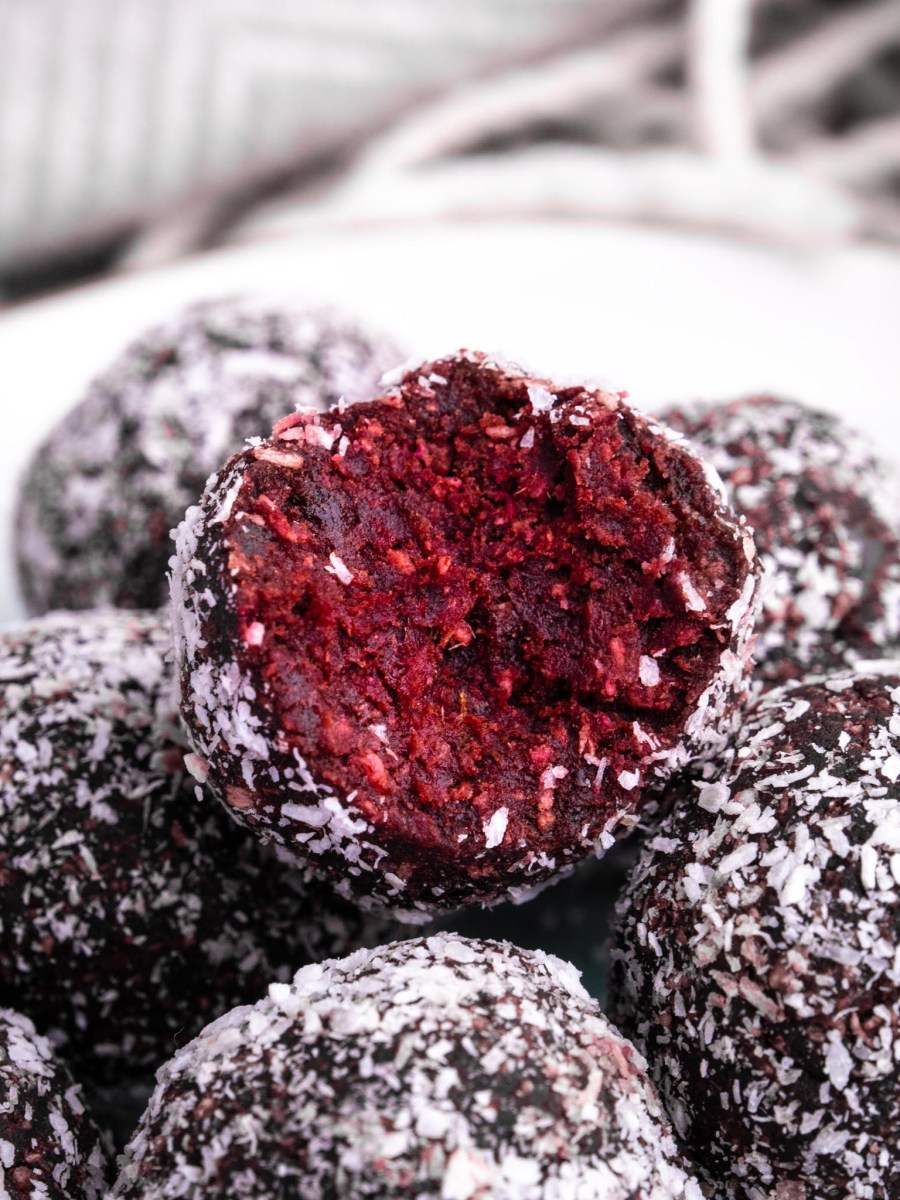 red velvet cake balls stacked on top of each other dusted with shredded coconut