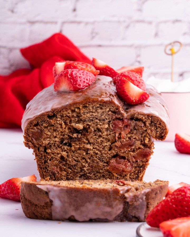 strawberry vegan banana bread sliced down middle to reveal moist fluffy centre studded with strawberries and topped with fresh fruit