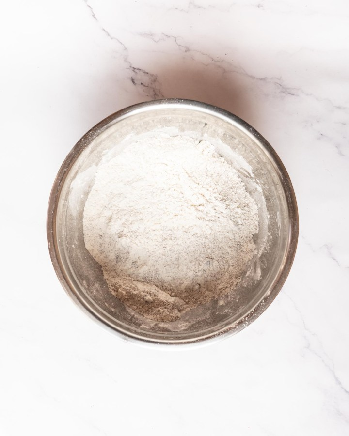 gluten-free flour in silver mixing bowl on white table