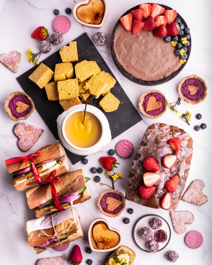 white table laden with cakes, tarts, cheese fondue for valentines day