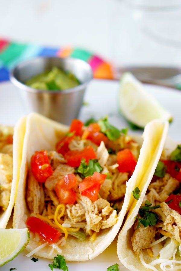 Close up picture of 3 chicken tacos with toppings.