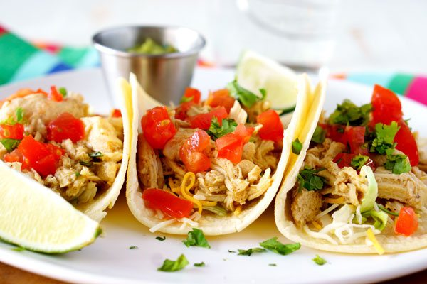 Chicken tacos on a white plate with cheese, tomatoes, and cilantro on top.