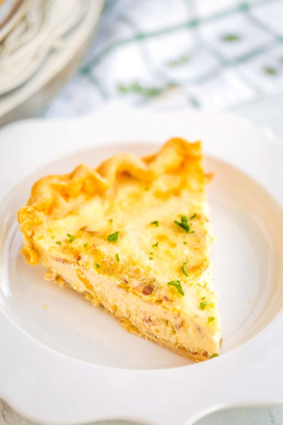 Close up picture of Homemade Quiche Lorraine slice on a white plate.