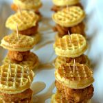 Two rows of chicken and waffles on a serving platter