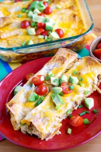 These Overnight Breakfast Enchiladas are EVERYTHING! They're loaded with hash browns, pinto beans, green chilies, bacon, eggs, enchilada sauce, and cheese!
