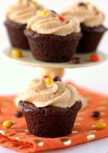 Mini brownie bite on an orange napkin with peanut butter icing and mini Reese's pieces.