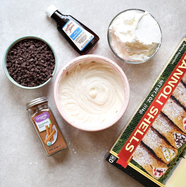 All of the ingredients for cannoli filling: whipped cream, ricotta cheese, vanilla, and dark chocolate.