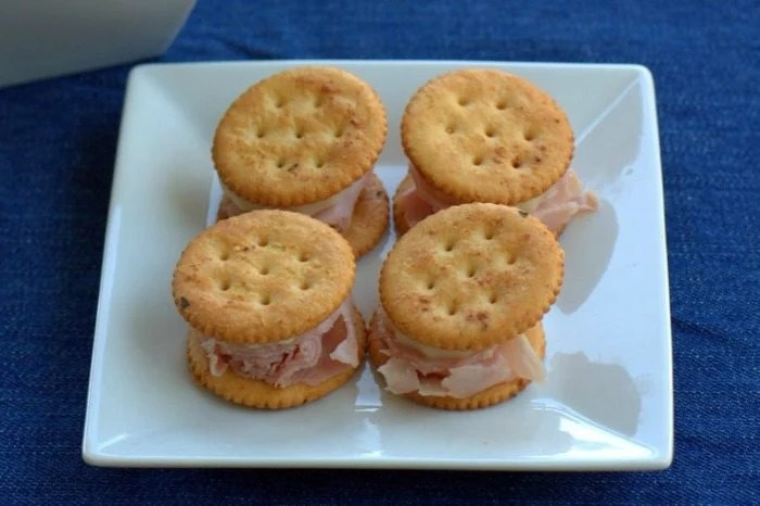 Ranch RITZ Crackers stacked with Ham and Cheese on a white plate.