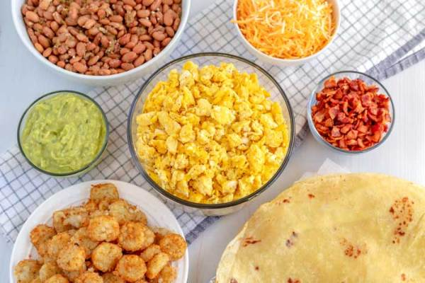All of the ingredients in bowls needed to make breakfast burritos.