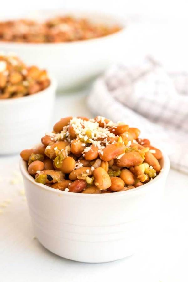 Green chile pinto beans served in white bowls.