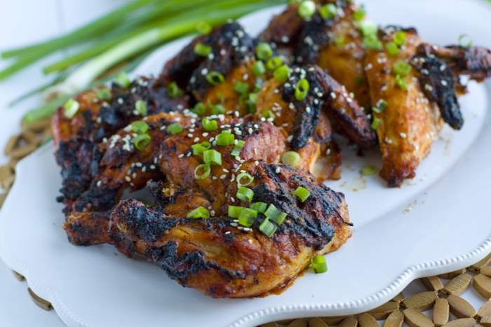 Game hens on a white platter sprinkled with chopped green onions and sesame seeds.