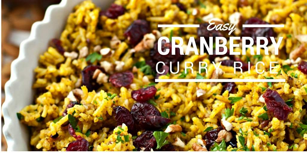 Close up picture of cranberry rice with pecans and curry in a white serving bowl.