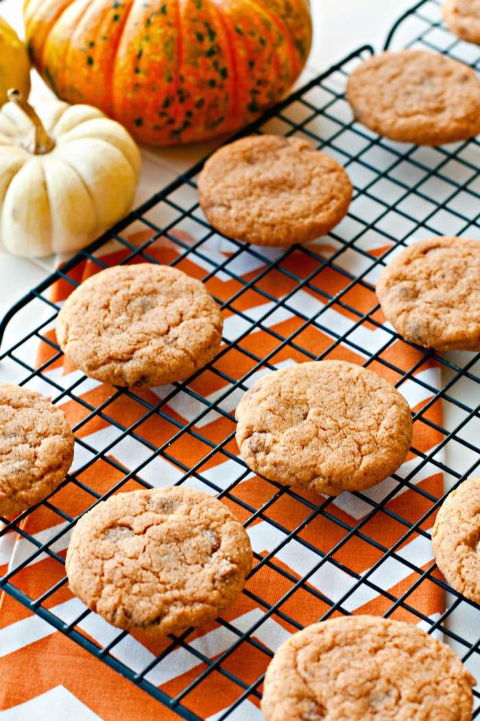 Rows on pumpkin pudding cookies on a wire backing rack cooling.