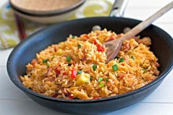 Hawaiian fried rice in a frying pan with a wooden spoon.