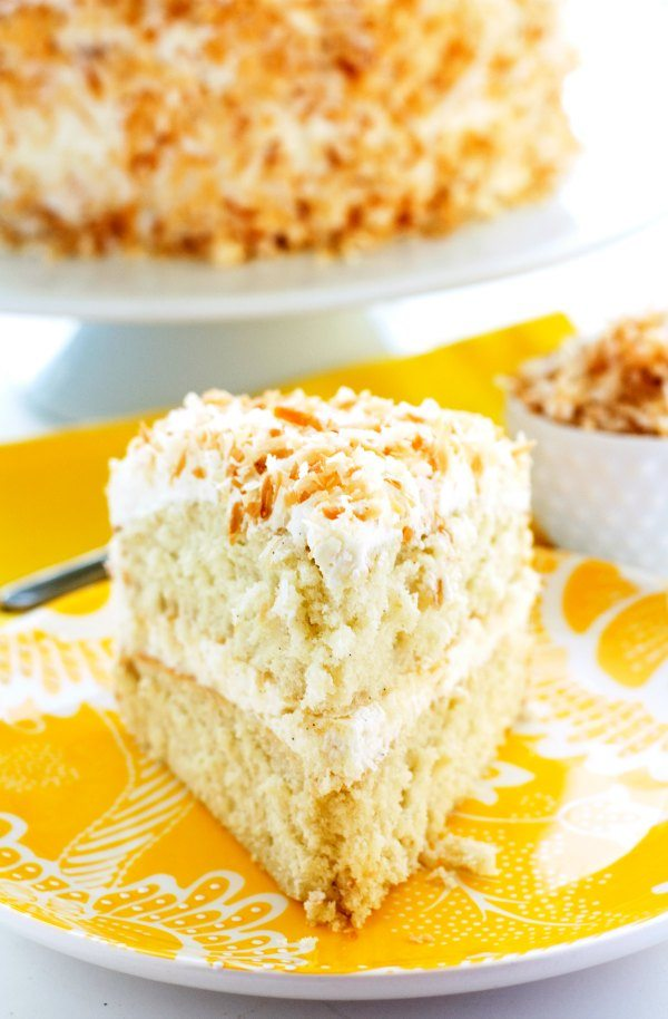 Thick slice of coconut cake that is on a vibrant yellow plate.