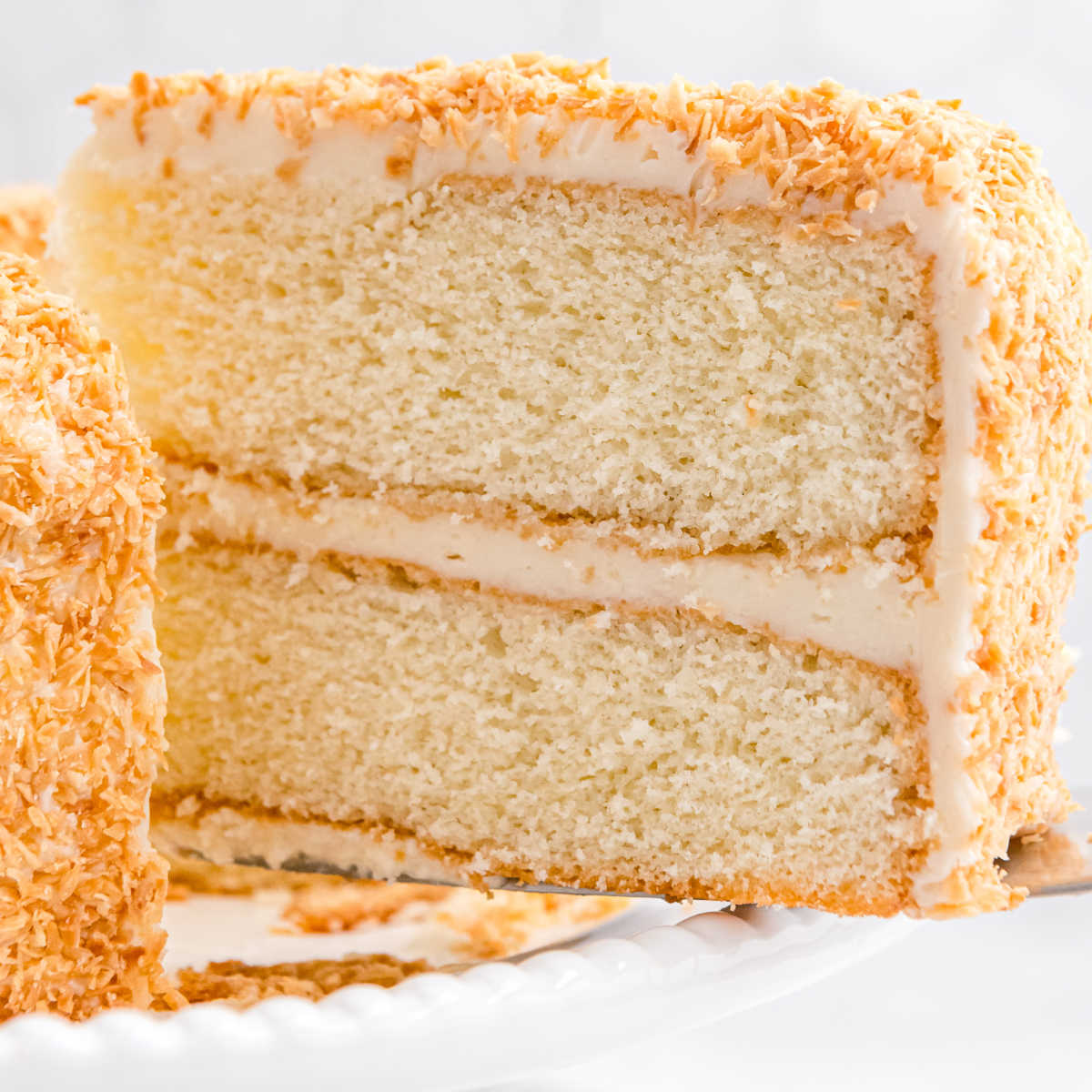 The finished coconut cake that is covered in coconut on a white cake stand.
