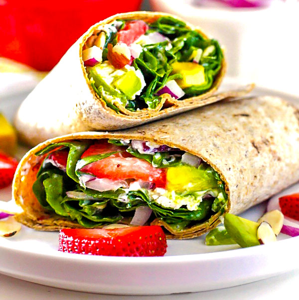 Strawberry Spinach Wraps on a white plate with strawberries, avocado, almonds, and red onions sprinkled around it.