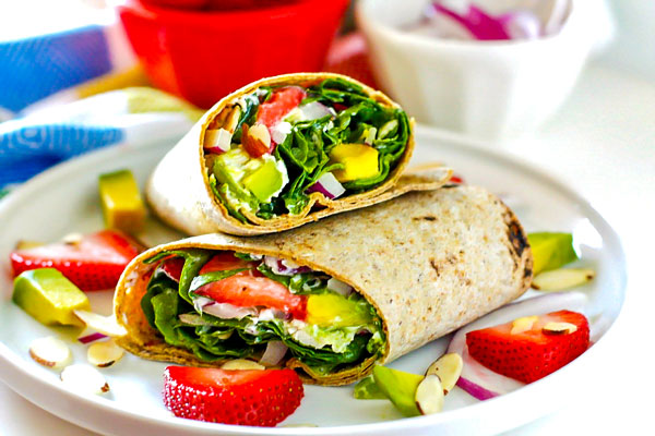 Spinach wraps stacked on each other on a white plate.