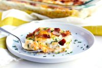 Pierogi-inspired lasagna on a plate with bacon and chives.