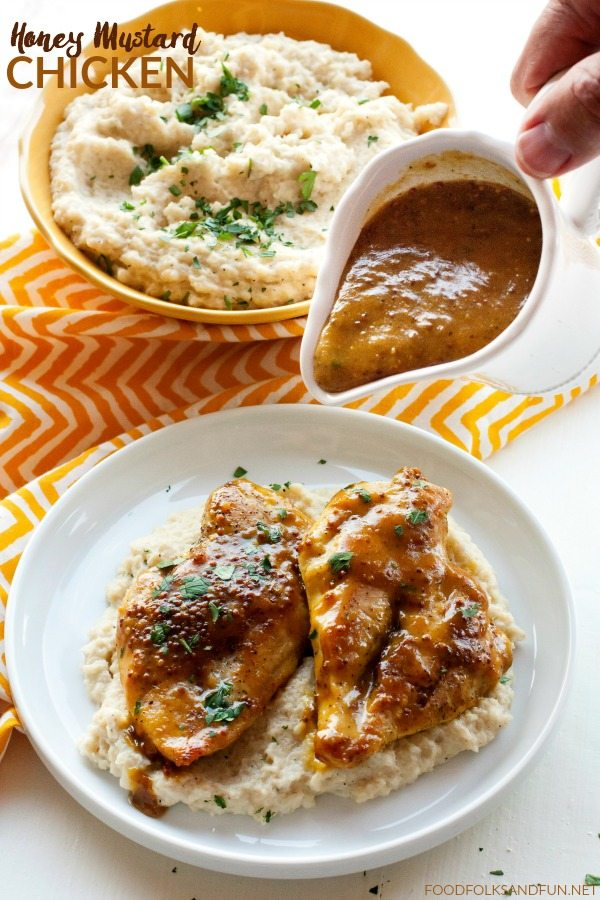Chicken on a plate with honey mustard sauce poured on top.