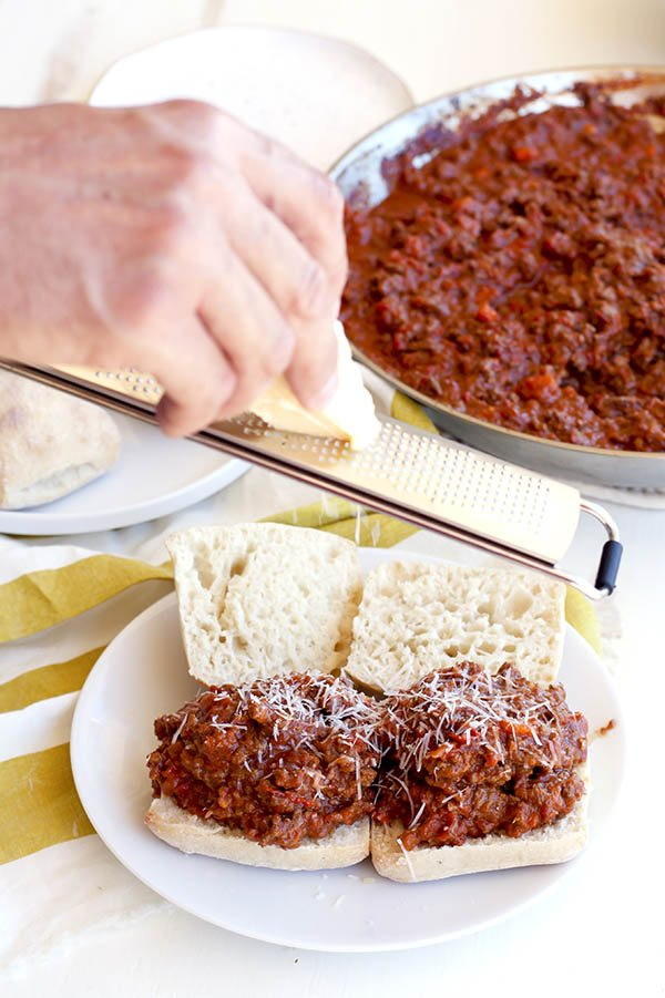 Cheese being grated on top of the bolognese.
