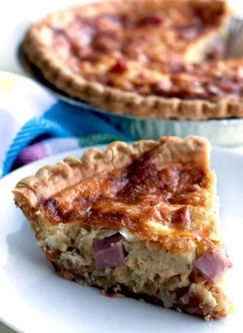 A close up of a slice of Ham and Cheese Quiche on a plate