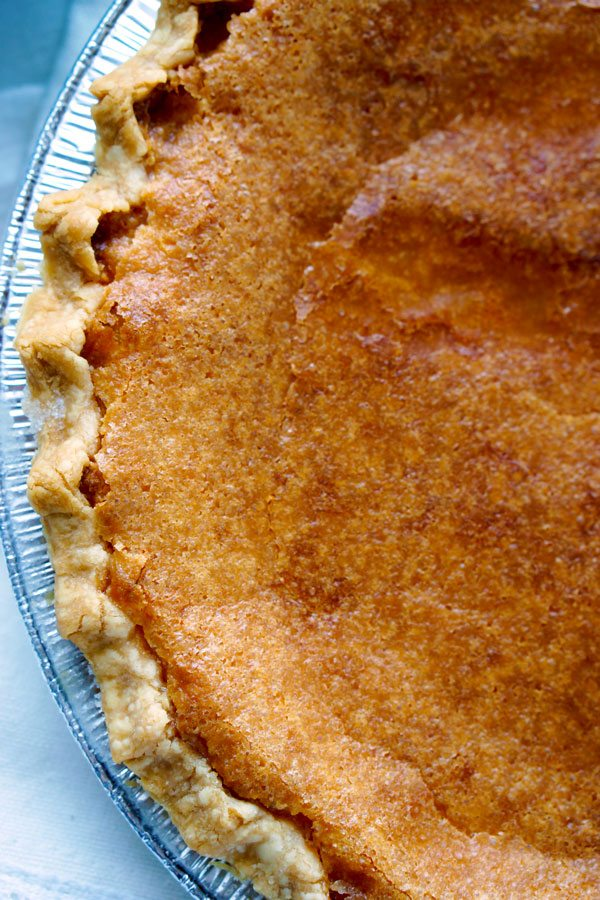 A close up picture of the crackly crust of a buttermilk pie.